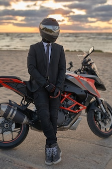 Shot of motorcyclist weared in black costume and helmet posing with his motorbike on beach.