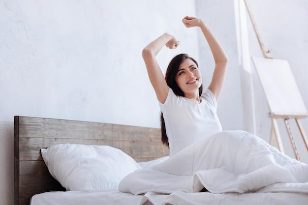 Кадр: женщина с каштановыми волосами, накрытая одеялом, сидит на кровати с раскинутыми руками