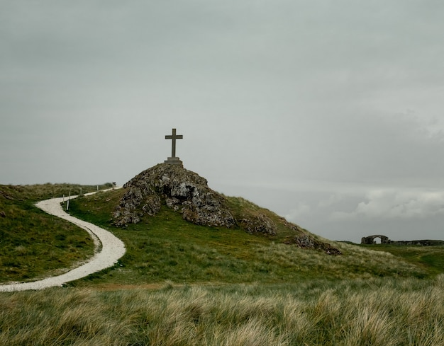 岩だらけの丘の上に置かれた台座の上に置かれた十字架のショット