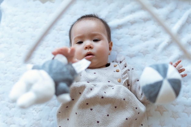 귀여운 여자 아이의 샷이 집에서 아이들의 뮤지컬 모바일 장난감을 보고 놀고 있습니다.
