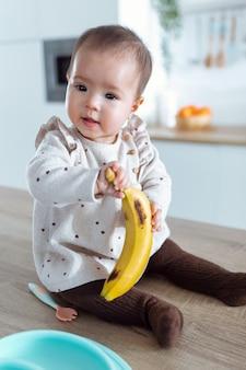 Снимок милой маленькой девочки, смотрящей в сторону и держащей банан, сидя на кухонном столе дома.