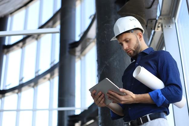 建設現場でデジタルタブレットを使用しているエンジニアのショット。このソフトウェアは私がすべてを追跡するのに役立ちます。