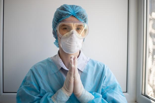 医療関係者保護装置を身に着けて祈っている女性のショット
