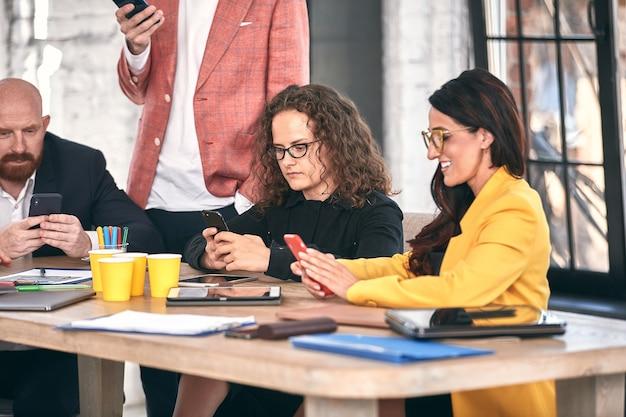 Выстрел группы молодых бизнес-профессионалов, встречающих разнообразную группу молодых дизайнеров, улыбающихся во время встречи в офисе.