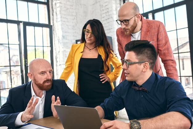 会議をしている若いビジネス専門家のグループのショット。オフィスでの会議中に微笑んでいる若いデザイナーの多様なグループ。