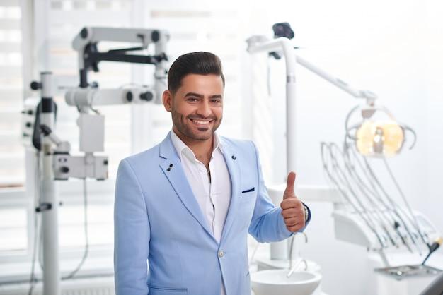 Выстрел из улыбающегося красивого бизнесмена, показывающего большие пальцы руки вверх, стоя в стоматологической клинике после устного осмотра, позитивность, счастье, благополучие, здоровье, медицина, люди, концепция.