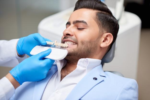Выстрел из красивого молодого человека на приеме у врача в офисе стоматолога. профессиональный стоматолог держит зубные протезы, сравнивая цвет и оттенок отбеливания здравоохранения.
