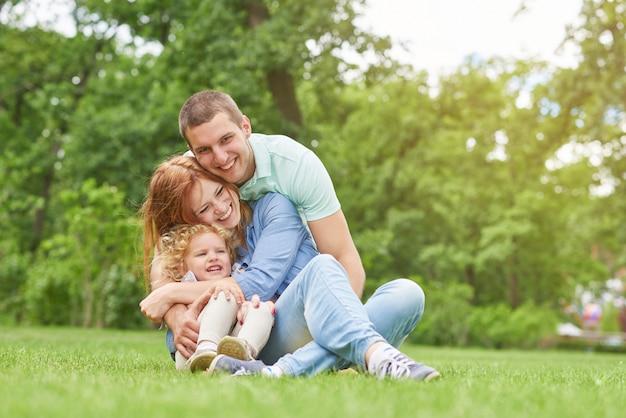 暖かい夏の日に屋外の公園の芝生の上に座って楽しんで幸せな若い愛情のある家族のショットハグし、寄り添うcopyspace両親は、カップル、子供、子供、娘、父、母を愛しています。