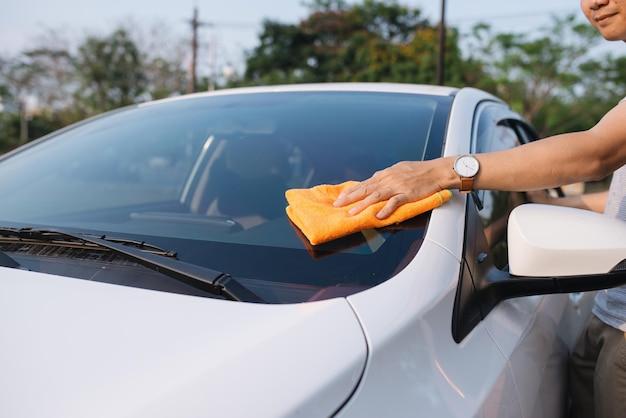 晴れた日にマイクロファイバーの布で車を掃除している幸せな若い男のショット。
