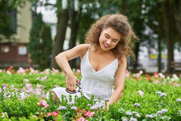 幸せな若い女のショットガーデニング笑顔copyspace楽しみレクリエーションは、田舎の家のコンセプトに住んでいる週末の休日をリラックスします。