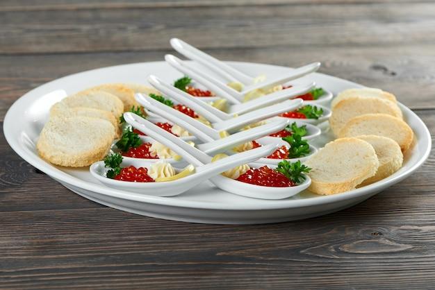 シャキッとしたラスクの珍味の近くに置かれたスプーンで提供される赤いキャシアとプレートのショットグルメグルメレストランメニュー部分シーフード装飾サービス高級カフェ料理のコンセプト。