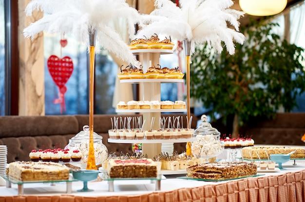 さまざまなおいしいデザートカップケーキとクリーミーなケーキ甘い砂糖を食べるカフェのお祝いの概念をたっぷりとレストランのテーブルのショット。