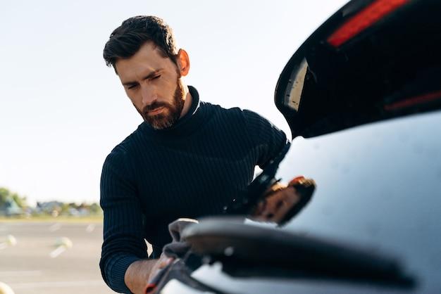 화창한 여름날 거리에서 시간을 보내는 동안 차의 몸을 청소하는 만족한 집중된 남자의 샷. 스톡 사진