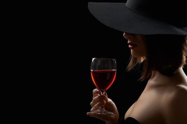 Выстрел из сексуальной женщины в черной шляпе, скрывающей ее лицо, пить вино