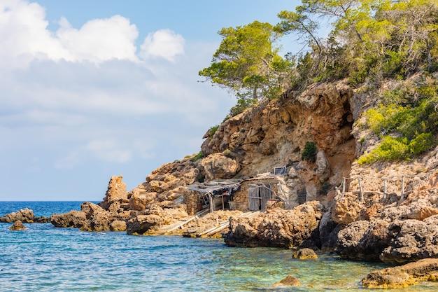 Снимок хижины на берегу моря, построенной под обрывом, окруженной большими каменными глыбами.