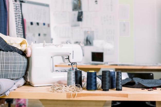 日当たりの良いファッションデザインスタジオのショット。私たちはミシンとテーブルの上にさまざまなミシン関連アイテム、カラフルな生地、吊り下げ服を見る。現代のミシンで仕立て屋の職場
