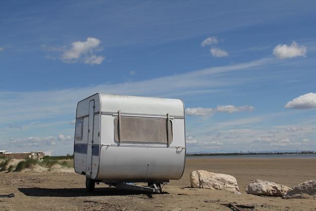地面にある白い古い旅行用トレーラーのショット