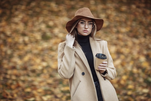 Выстрел молодой привлекательной женщины, одетой в пальто и фетровую шляпу на фоне опавших листьев в осеннем парке