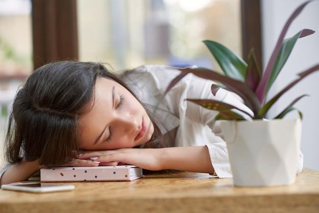 Выстрел из молодой красивой женщины спит на свой ноутбук после изучения трудно в местном кафе copyspace устали истощены студента жизнь кампуса колледж университет релаксация спит.