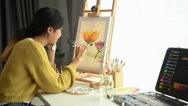 Снимок молодой художницы, работающей над живописью в студии