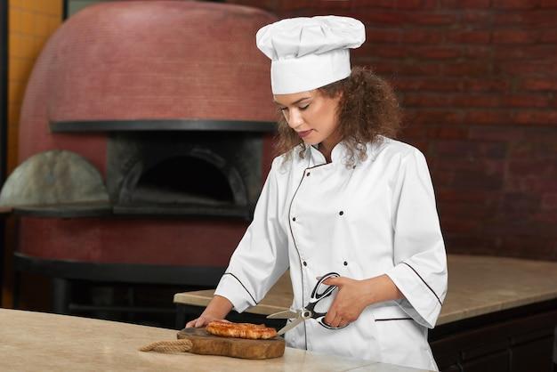 Выстрел молодой женщины-шеф-повара, готовящей куриный стейк на гриле на кухне, режущий мясо ножницами.