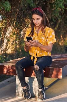 ベンチに座っている間彼女の電話を見ている若い女の子のショット