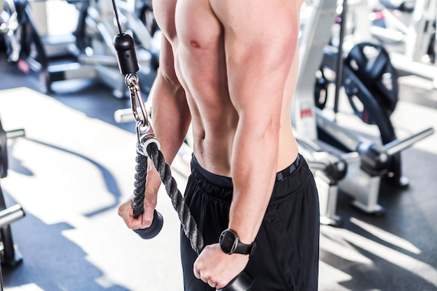Выстрел из молодого мускулистого мужчины, делающего трицепс в тренажерном зале. горизонтальное фото