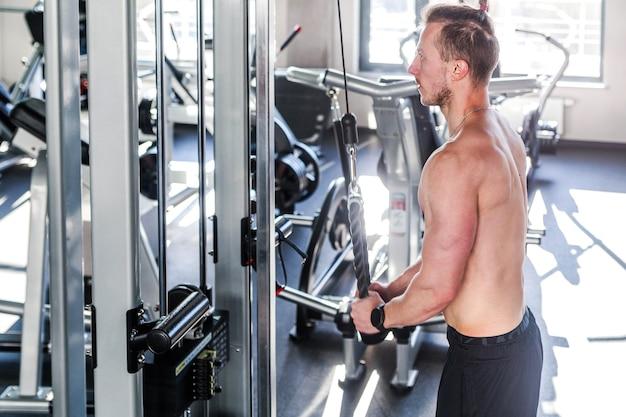 Выстрел из молодого мускулистого мужчины, делающего трицепс в тренажерном зале. вид со спины. горизонтальное фото