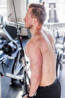 Выстрел из молодого мускулистого мужчины, делающего трицепс в тренажерном зале. вид со спины. вертикальное фото