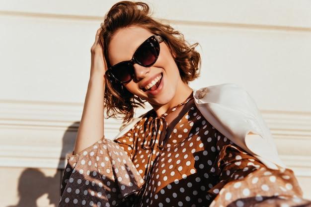 검은 선글라스에 사랑스러운 기쁘게 여자의 총. 행복을 표현하는 세련된 곱슬 아가씨의 야외 촬영.