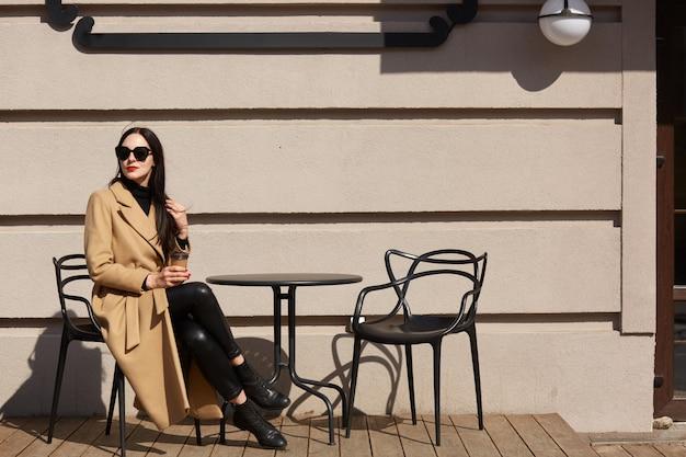 거리 야외 카페에서 테이블에 앉아 커피 또는 차를 마시는 세련된 코트를 입고 사랑스러운 젊은 갈색 머리 여자의 총