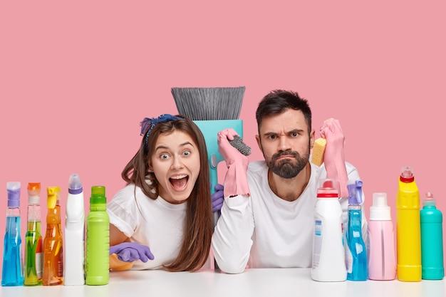 Удивленная молодая женщина и грустный недовольный мужчина сидят за столом с моющими средствами и моют мебель в квартире