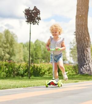 Выстрел очаровательной маленькой девочки, улыбающейся верхом на скутере на сельской дороге в теплый солнечный день, copyspace, детство, счастье, эмоции, беззаботная деятельность, спорт.