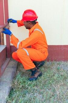 Снимок черного мужчины, снимающего замеры вне дома