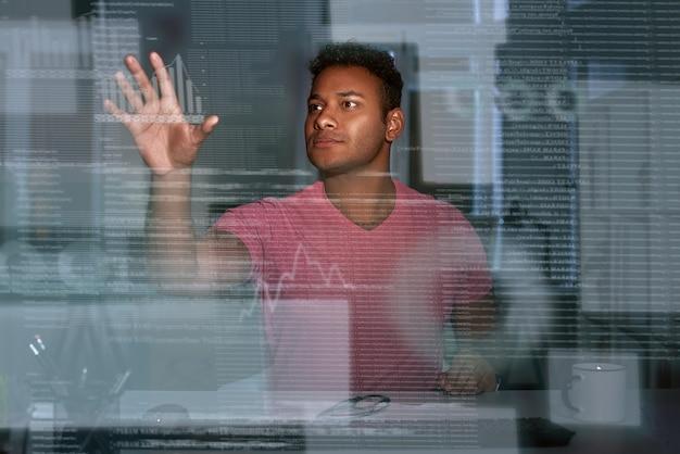 빅 데이터 작업을 하는 인도 데이터 분석가의 사진입니다. 그는 안경을 들고 집중하고 사려깊은 것처럼 보입니다. 빅데이터 개발자. 비즈니스 인텔리전스