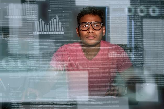 빅 데이터로 작업하는 인도 프로그래머의 샷. 그는 안경을 들고 집중하고 사려깊은 것처럼 보입니다. 빅데이터 개발자. 비즈니스 인텔리전스