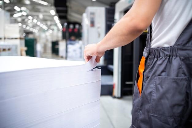 印刷のためにオフセット機に白紙を置く準備ができている印刷作業員のショット