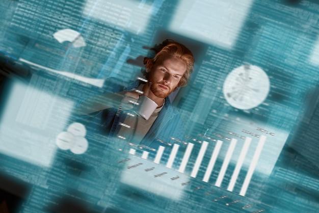 빅 데이터를 다루는 젊은 빨간 머리 데이터 분석가의 사진. 그는 집중하고 사려깊은 것처럼 보이며, 커피 작물을 들고 있습니다. 빅데이터 개발자. 비즈니스 인텔리전스