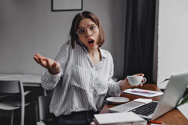 Выстрел сердитой женщины в очках с чашкой кофе в руках. деловая женщина смотрит в камеру в изумлении, разговаривает по телефону на рабочем месте.