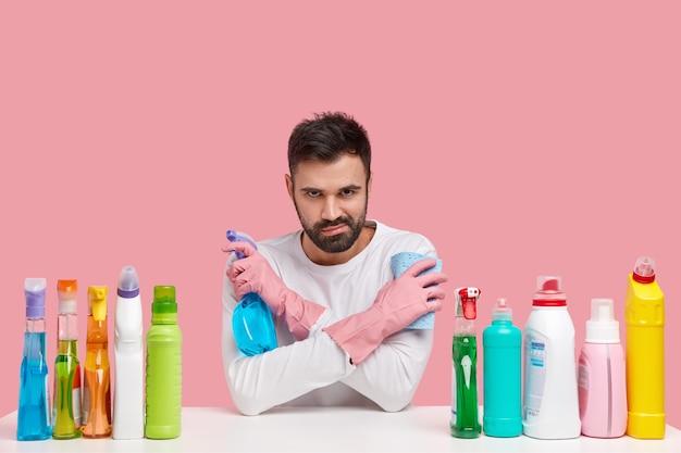 魅力的な男のショットは、手を交差させ、洗濯スプレーとぼろきれを運び、暗い表情で見え、カジュアルな服を着ています