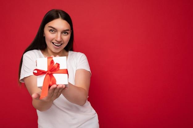 Выстрел привлекательной позитивной улыбающейся молодой женщины брюнетки изолированной