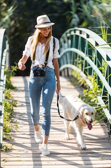 Выстрел из привлекательной молодой любительской фотографии женщины, идущей со своей собакой, пересекающей мост в парке.