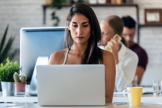 사무실에서 컴퓨터로 작업하는 매력적인 젊은 비즈니스 여성의 총. 배경에는 사무실에서 함께 일하는 동료들.