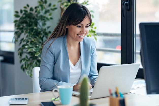 Выстрел из привлекательной молодой деловой женщины, работающей с компьютером, сидя за столом в современном офисе запуска.