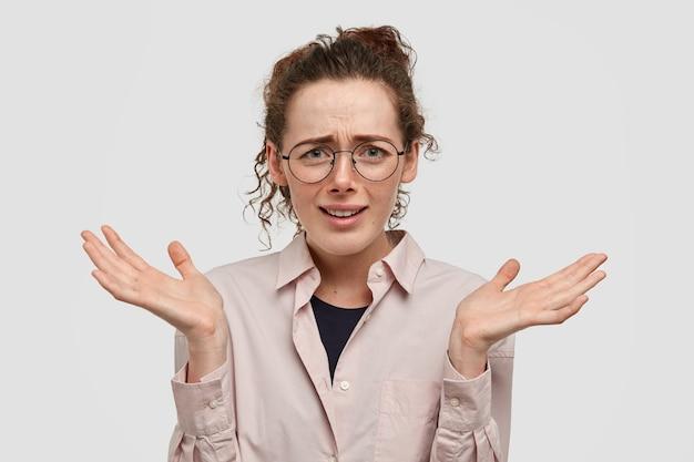 躊躇する表情、肩をすくめ、手のひらを上げたままの魅力的な若い女性のショットは、白い壁に隔離された無知な外観をしています。困惑と疑いの概念。