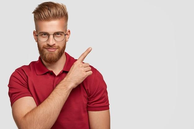 厚いひげを持つ魅力的な若い生姜の男性のショット、右上隅にポイント、自信を持って顔の表情を持っている、コピースペースで白い壁に隔離された赤いtシャツを着ています