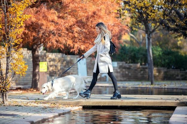 Выстрел привлекательной молодой женщины, идущей со своей прекрасной собакой на мосту в парке осенью.