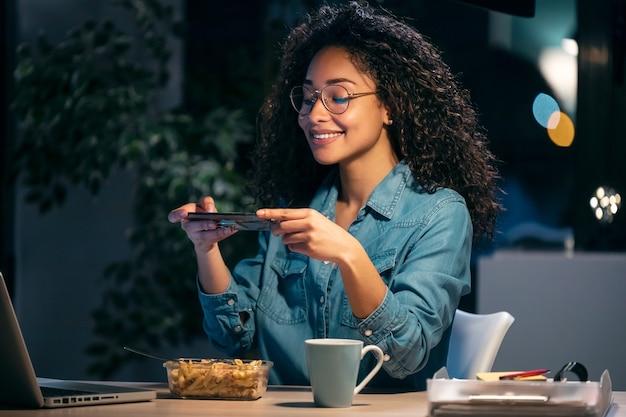 オフィスに座ってパスタを食べながらスマートフォンで写真を撮る美しいアフロ若いビジネス女性のショット。
