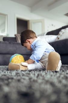집 거실 바닥에서 공을 가지고 노는 아름다운 아기의 사진.