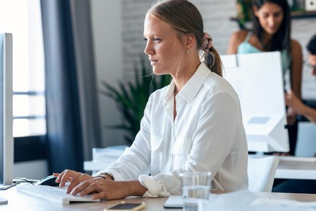 컴퓨터 작업을 하는 아름 다운 금발 비즈니스 젊은 여자의 쐈 어. 배경에는 사무실에서 함께 일하는 동료들.